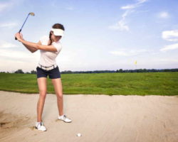 Beginner woman golfer swinging at golf ball